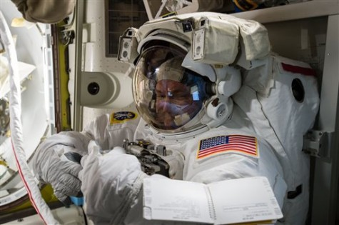 In this photo provided by NASA and posted on Twitter on Oct. 26, 2015, astronaut Scott Kelly tries on his spacesuit inside the U.S. Quest airlock of the International Space Station. NASA opened its astronaut-application website Monday, Dec. 14, 2015. It's accepting applications through Feb. 18, 2016.