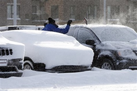 A car dealership employee cleans off a vehicle, Wednesday, Feb. 3, 2016, following a snowstorm which dumped a foot of snow in Southern Minnesota. (AP Photo/Jim Mone)