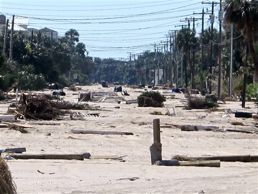 Debris from the storm surge of Hurricane Matthew litters the ocean front street in Edisto Beach, S.C., on Monday, Oct. 10, 2016. Town officials say the storm washed between 3 and 4 feet of sand onto the street and the community took its worst hurricane hit since Hurricane David back in 1979. (AP Photo/Bruce Smith)