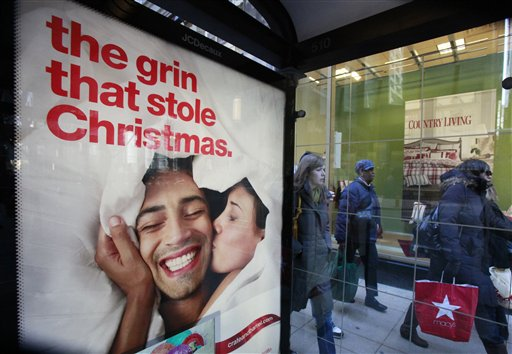 Shoppers walk past a Christmas advertisement outside Sears Friday, Nov. 27, 2009, in downtown Chicago as consumers around the nation crowded stores and malls on Black Friday, the traditional start of the holiday shopping season. (AP Photo/Charles Rex Arbogast)