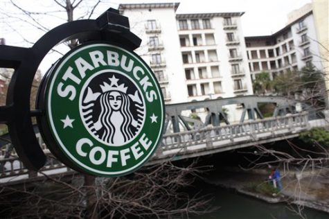 A sign outside a Starbucks hangs over the Riverwalk with the Navarro Street bridge in the background in San Antonio, Texas.