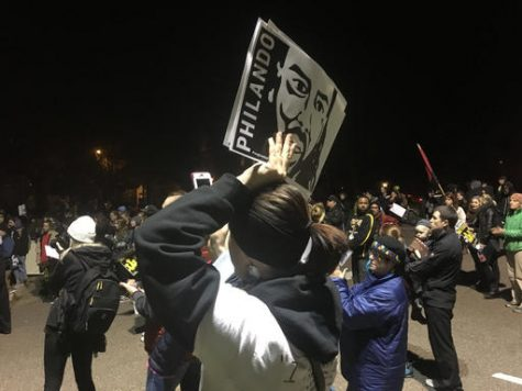 A woman holds a sign with Philando Castile's image during a rally in St. Paul, Minn., after a police officer is charged in Castile's fatal shooting in Falcon Heights, Wednesday, Nov. 16, 2016.  (AP Photo/Jeff Baenen)
