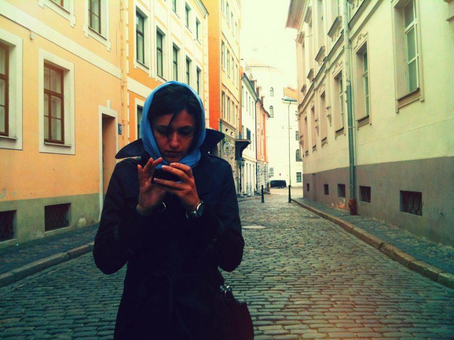 A student absorbed into her phone while walking on the street.