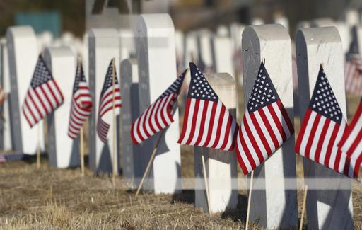 American flags stand next to the markers amid the headstones of veterans and their family members to mark Veterans Day in Riverside Cemetery on Friday, Nov. 11, 2016, in Denver. (AP Photo/David Zalubowski)
