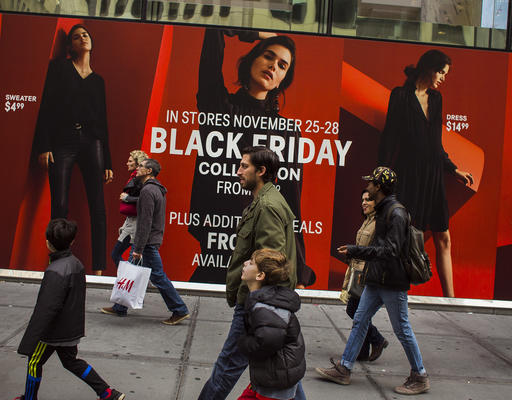 Shoppers pass by a retail store as they walk along Fifth Avenue on Black Friday in New York, Friday, Nov. 25, 2016. Shoppers were on the hunt for deals Friday as malls opened for what is still one of the busiest days of the year, even as the start of the holiday season edges ever earlier. (AP Photo/Andres Kudacki)